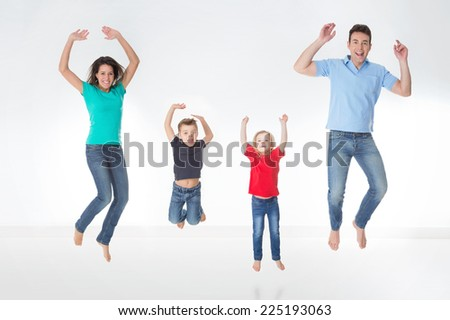 mother, father and their children jumping together - stock photo