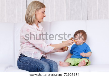 Mother feeding baby fruit squash - stock photo