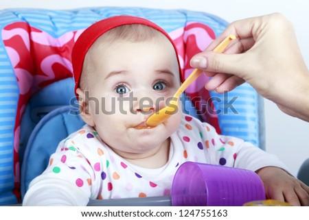 Mother feeding baby girl - stock photo