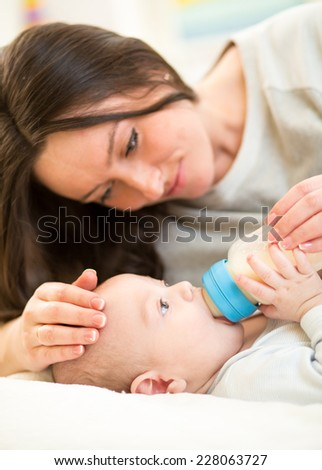 mother feeding baby son with a milk bottle at home - stock photo