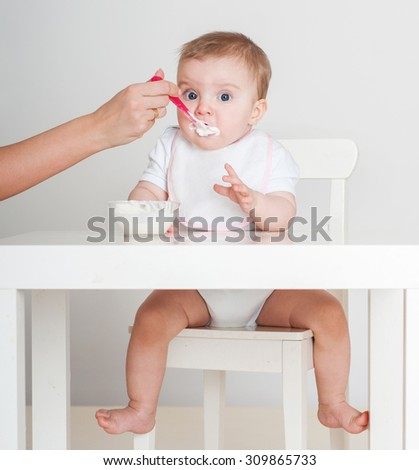 Mother feeding baby with a spoon. Spoon-feed. - stock photo