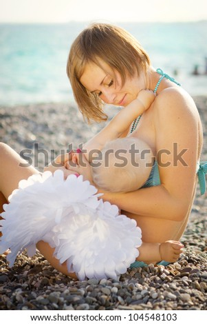 Mother feeding baby with angel wings - stock photo