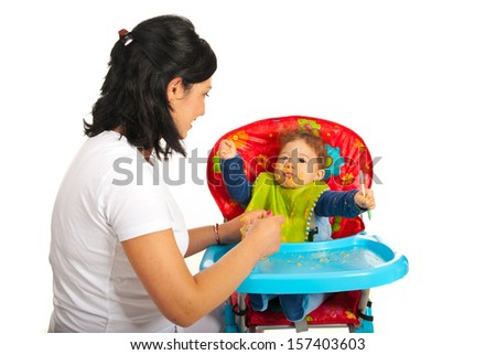 Mother feeding baby with puree in their home - stock photo