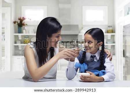 Mother feeding daughter breakfast at home - stock photo