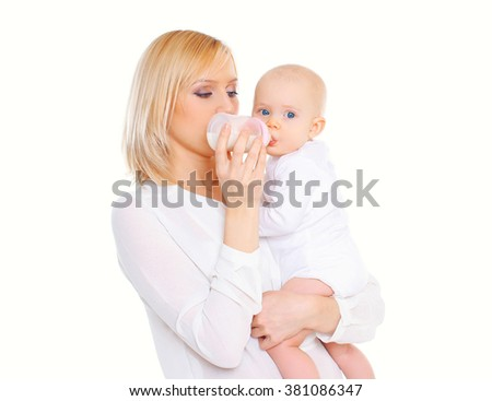 Mother feeding from bottle her baby over white background - stock photo