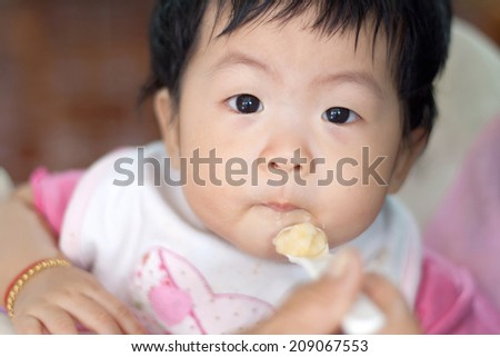 Mother feeding happy little cute daughter, asia - stock photo