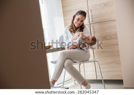 Mother feeding her baby boy. - stock photo