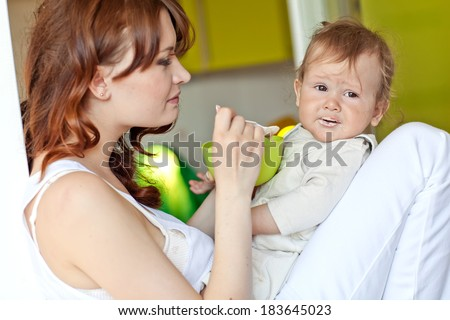 Mother feeding her baby with a spoon. Mother giving food to her adorable baby at home - stock photo