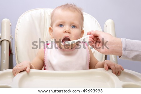 Mother feeding her happy little cute daughter - stock photo
