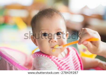 mother feeding her 7 months baby. - stock photo