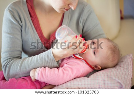 Mother feeding infant girl with a milk bottle - stock photo