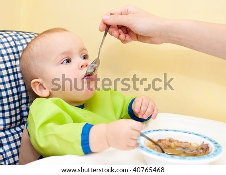 Mother feeding little baby girl in a highchair - stock photo