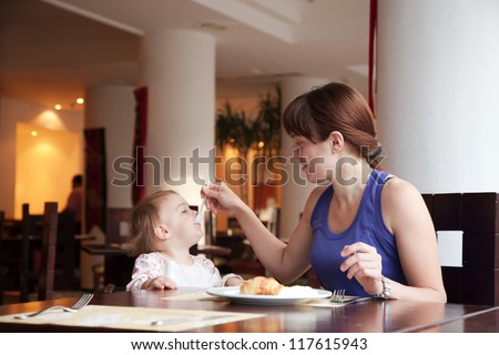 Mother feeding year-old child at cafe - stock photo