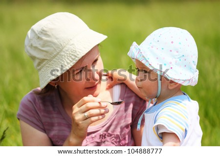 Mother feeds the baby on nature background - stock photo