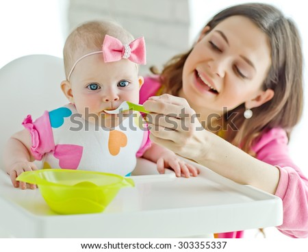 mother feeds the child - stock photo