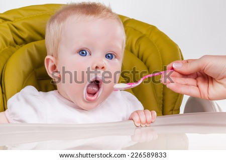 Mother feeds the child with a spoon - stock photo