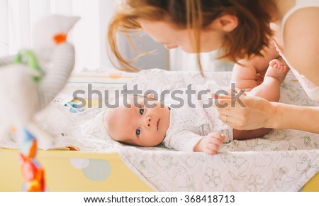 Mother gently care of baby on the changing table at home - stock photo