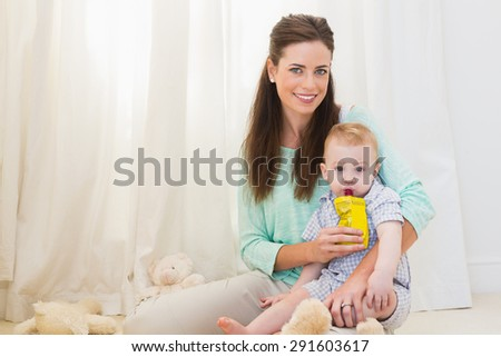 Mother giving baby a drink at home - stock photo