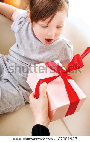 Mother giving birthday gift for baby - stock photo