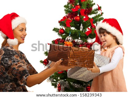 Mother giving Christmas gifts to her daughter in front of tree - stock photo