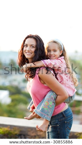 Mother giving daughter piggyback ride outdoors smiling - stock photo