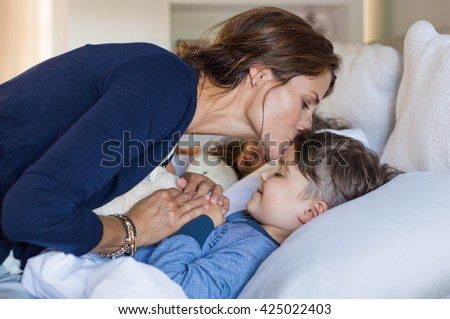 Mother giving good night kiss to sleeping son. Lovely mother putting son to bed. Happy young loving mother kisses son on forehead. - stock photo