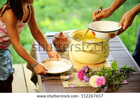 mother giving her daughter fresh soup - stock photo
