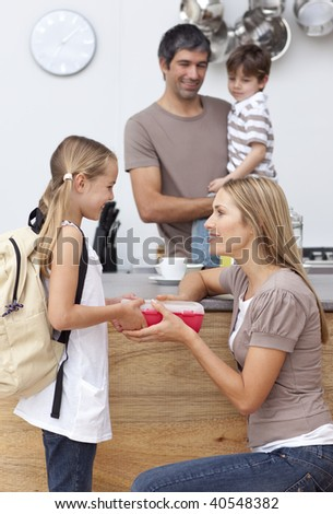 Mother giving her daughter the school lunch in the kitchen - stock photo