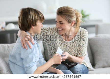 Mother giving money to adolescent for reward - stock photo
