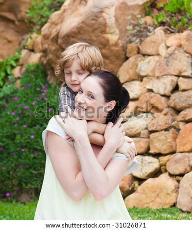 Mother giving son piggyback in park - stock photo