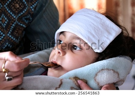 Mother giving syrup to her ill kid. - stock photo