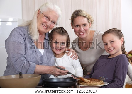 Mother, grandmother, and girls cooking pancakes - stock photo