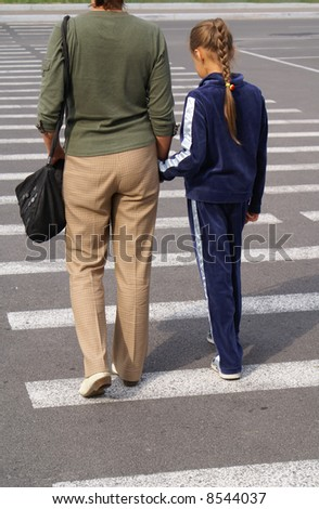 Mother guides her daughter across a street - stock photo