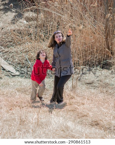 Mother guiding son: Mom raised her hand up and showing something to his son outdoors - stock photo