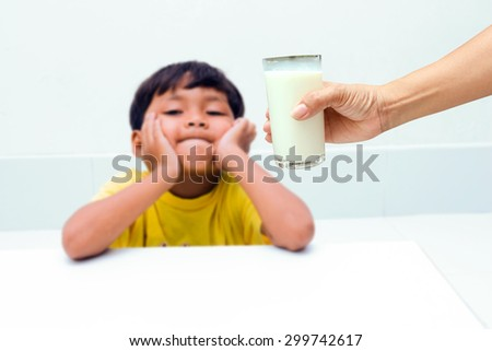 Mother hand holding a glass of milk for a little boy, who do not want to drink milk from glass. - stock photo