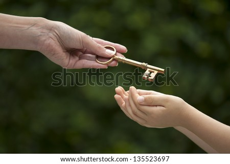 mother handing key to daughter - stock photo