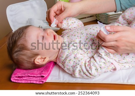 Mother hands cleaning eyes of baby with physiological serum in a cotton - stock photo