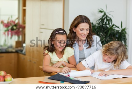 Mother having a look at her children's homework - stock photo