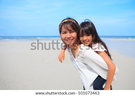 Mother having daughter a piggyback at the beach - stock photo
