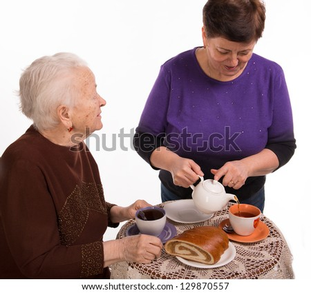 Mother having tea with her daughter on a white background - stock photo