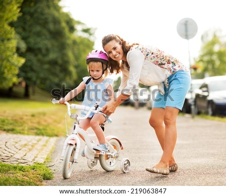 Mother helping baby girl riding bicycle - stock photo