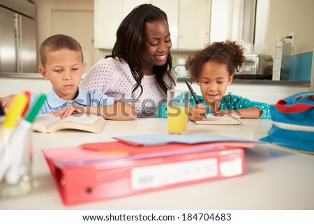 Mother Helping Children With Homework At Table - stock photo