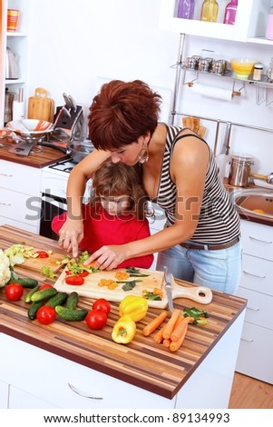 Mother helping daughter making salad - stock photo