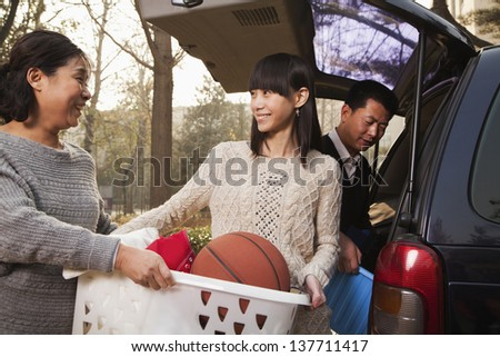 Mother helping daughter unpack car for college, Beijing - stock photo