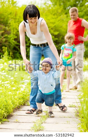 Mother helping her baby son to make first steps - stock photo