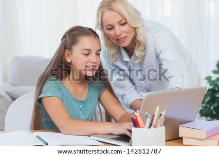 Mother helping her daughter to do homework with a laptop - stock photo