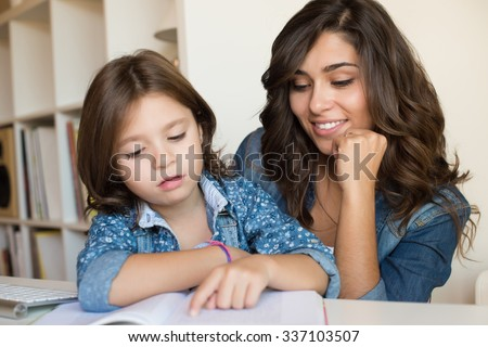 Mother helping her little child with homework - stock photo