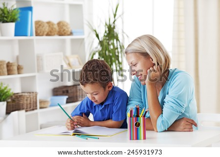 Mother helping her son with homework - stock photo