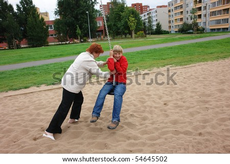 Mother helping his son play  on the playground - stock photo