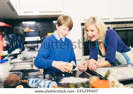 Mother helps her son making cookies in a kitchen - stock photo